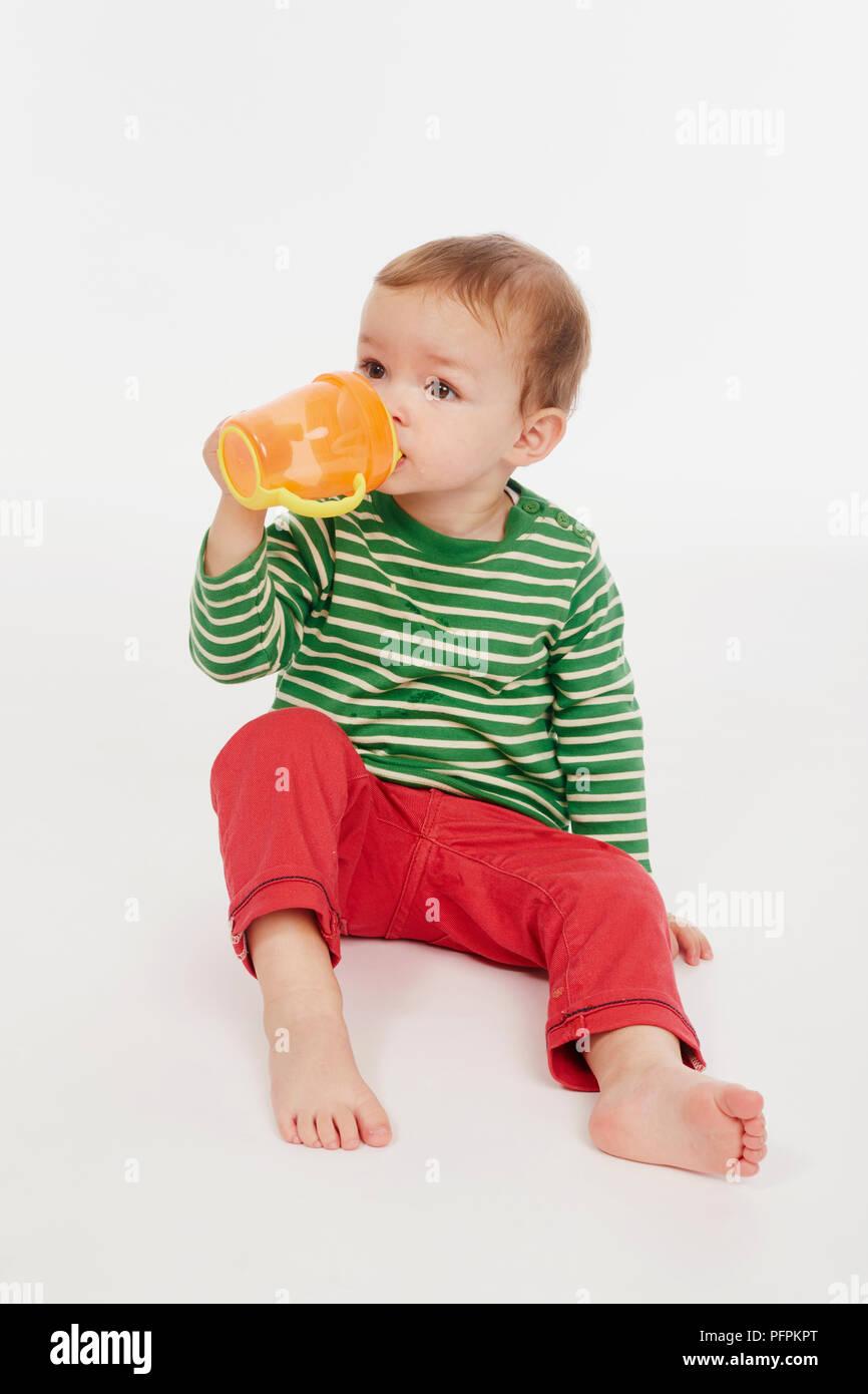 Little boy in green stripey top drinking from beaker (Model age - 22 months) - Stock Image