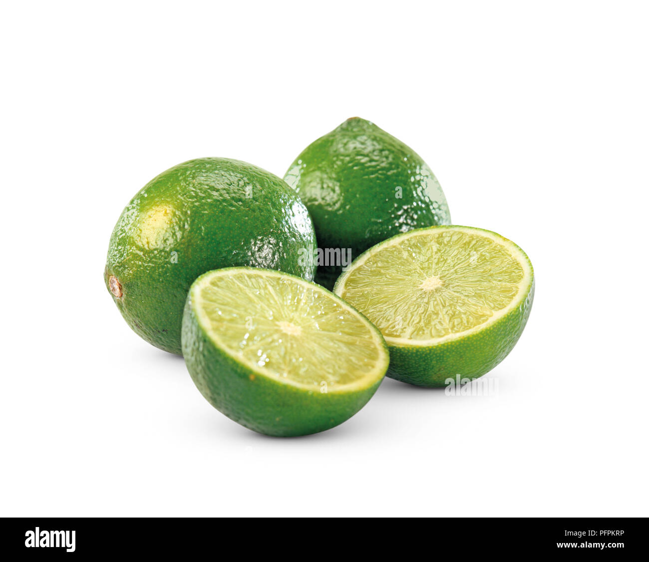 Two whole limes, and two halves, close-up - Stock Image