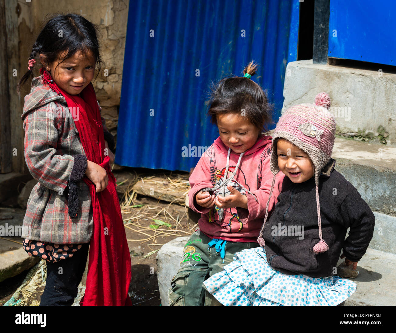 GHALEGAUN, NEPAL - CIRCA MAY 2018: Three young Nepali girls playing outside their home. - Stock Image