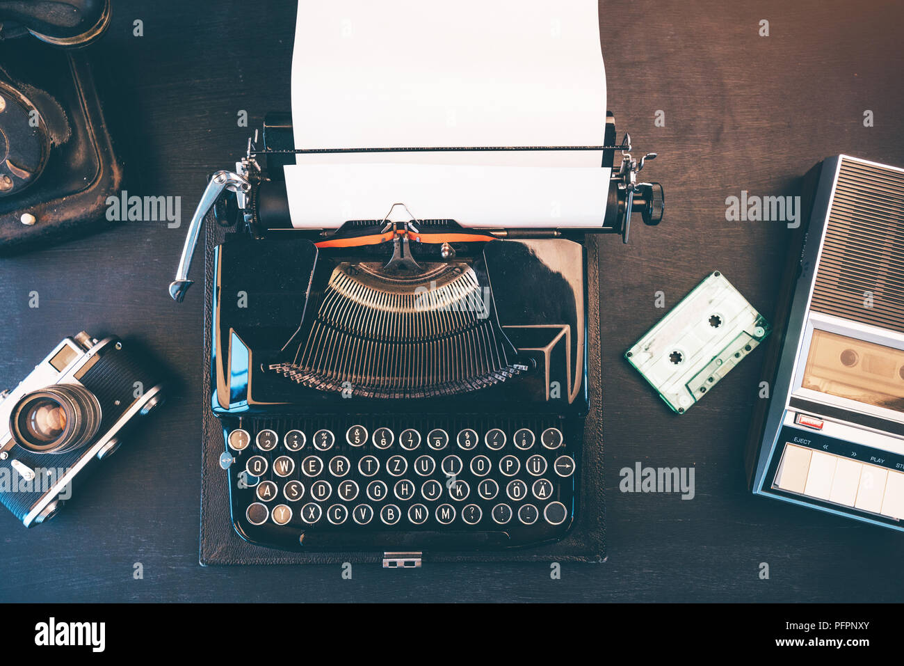 Top view of vintage journalist workspace with telephone, typewriter and audio cassette tape player - Stock Image