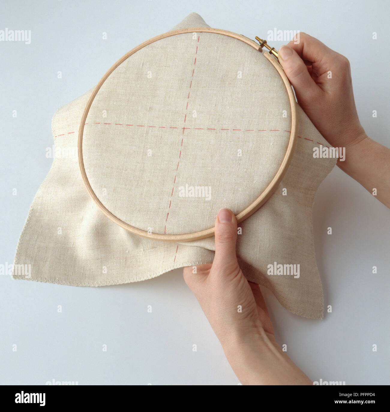 Woman\'s hands mounting fabric on embroidery hoop or tambour frame ...
