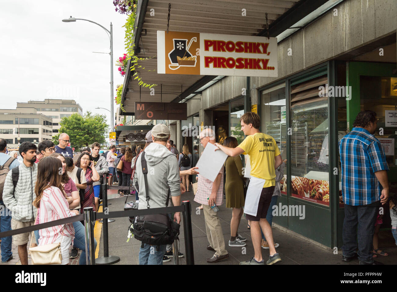 Visitors wait for their turns in line to taste piroshki in front of Piroshky Piroishky at Pike Place Market, Seattle, USA. - Stock Image