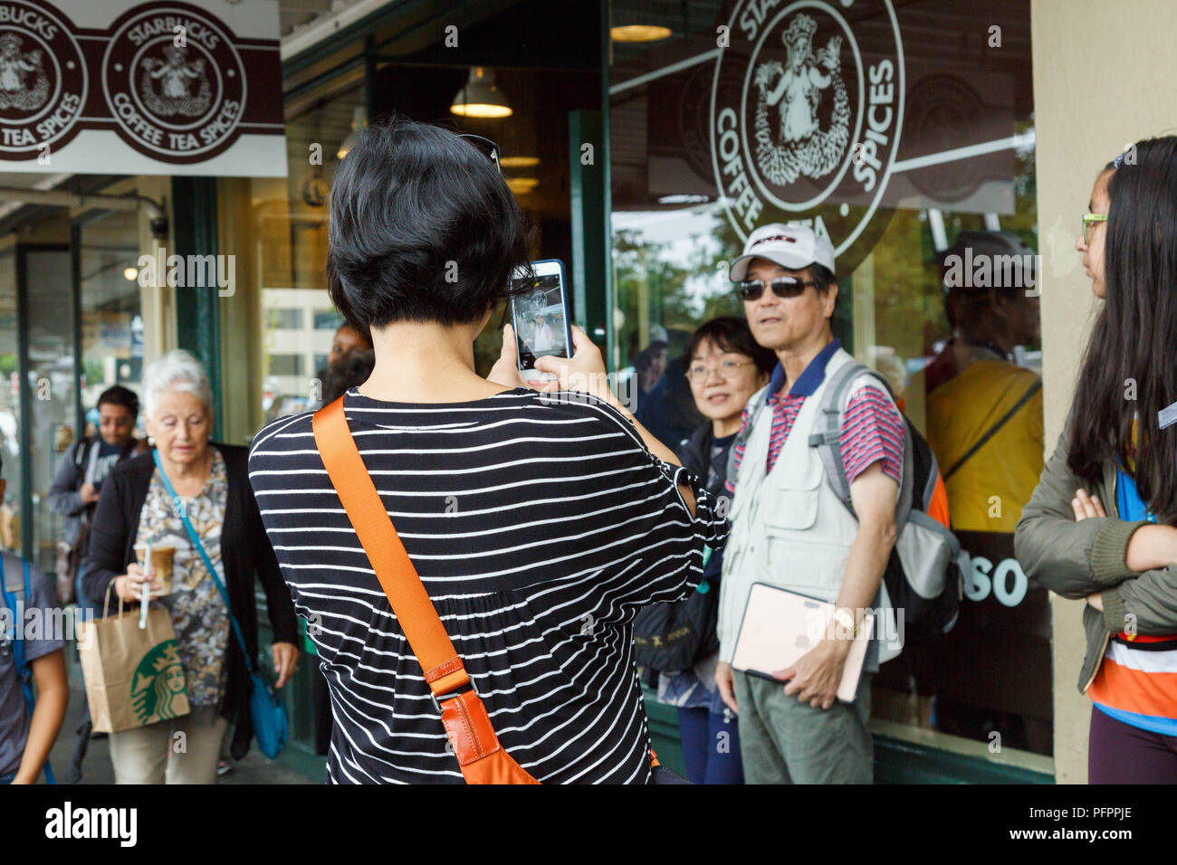 Visitors take pictures in front of original logo printed window of Starbucks Coffee flagship store at Pike Place Market in Seattle, USA. - Stock Image