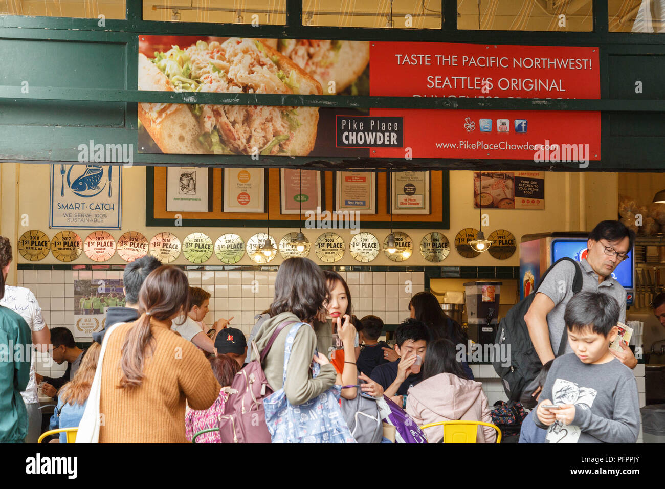 people wait in a long line to taste at the restaurant Pike Place Chowder which is very well known for their New England Clam Chowder in Seattle, USA. - Stock Image