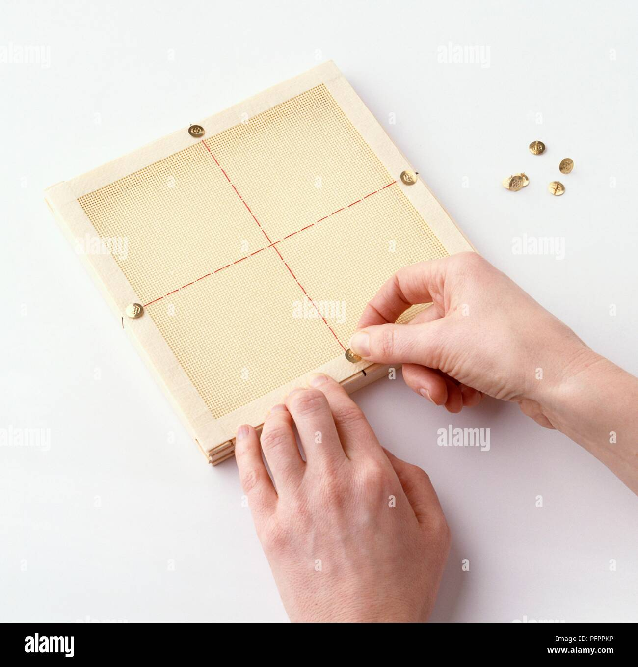 Using push pins to attach canvas to artist's frame - Stock Image