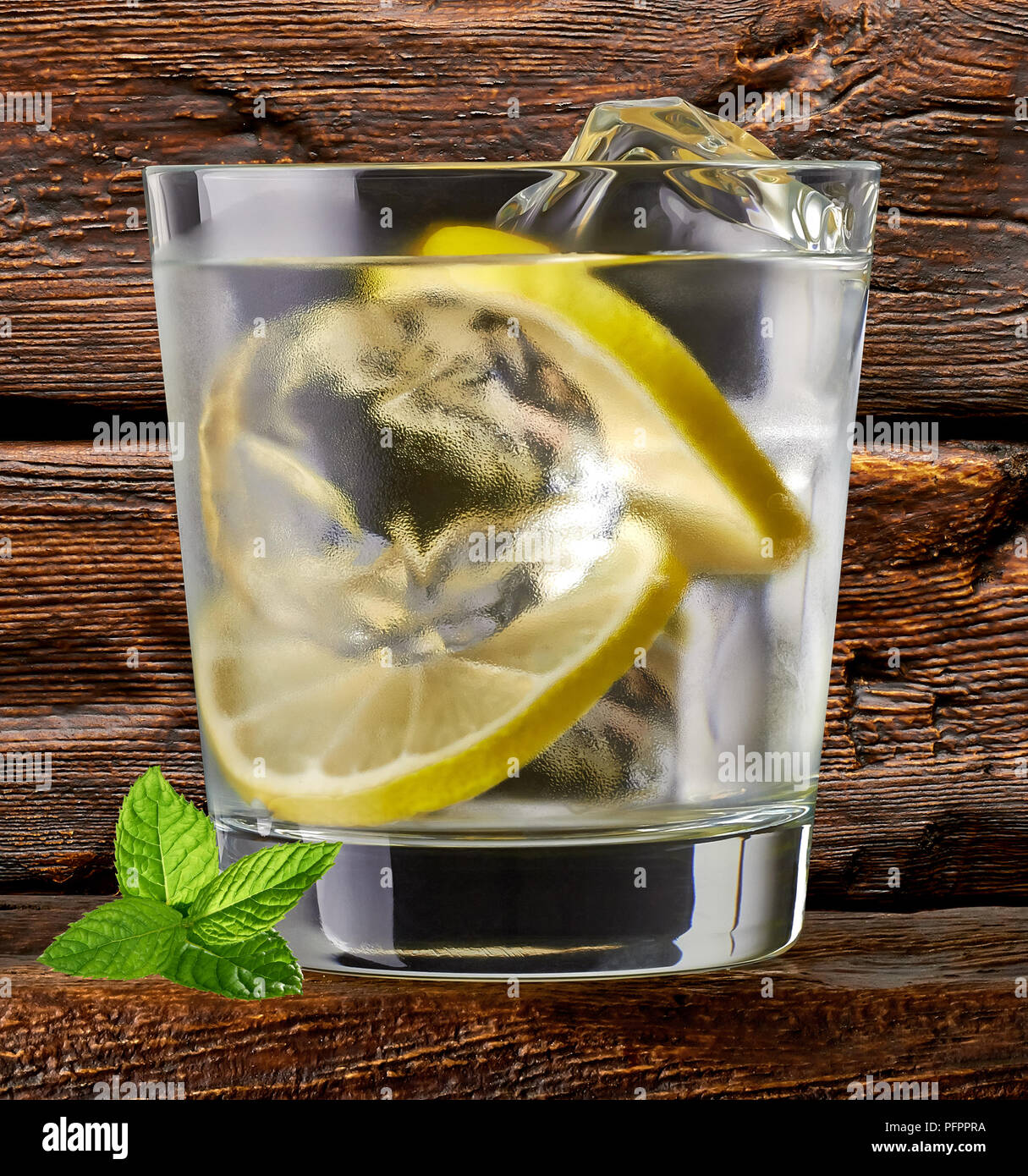 Gin tonic, vodka or rum with lime wedges on wooden table and background - Stock Image