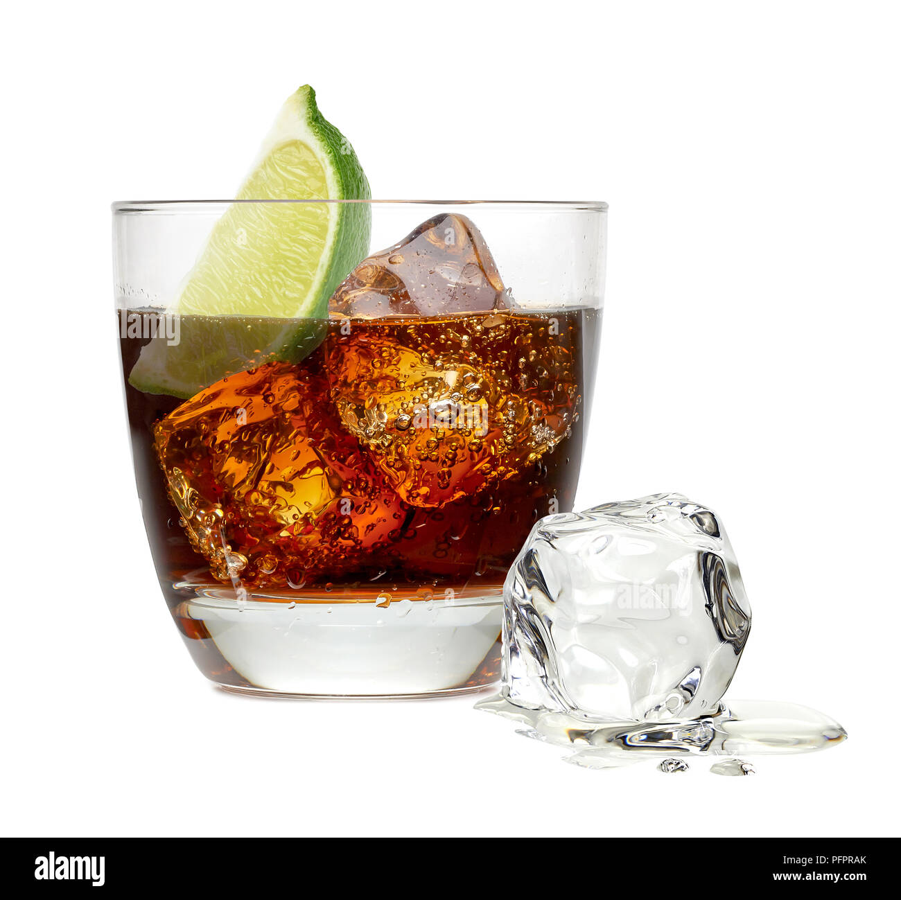 Cuba libre cocktail with ice cubes and lime wedge in rocks glass isolated on white background - Stock Image