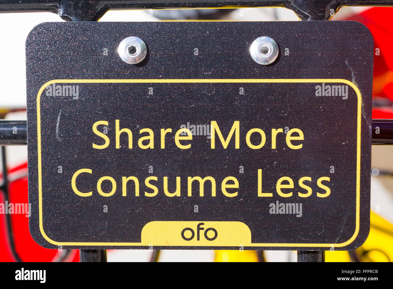 Share more consume less written on the front basket of an Ofo bike, the world's first and largest station-free bike share platform - Stock Image