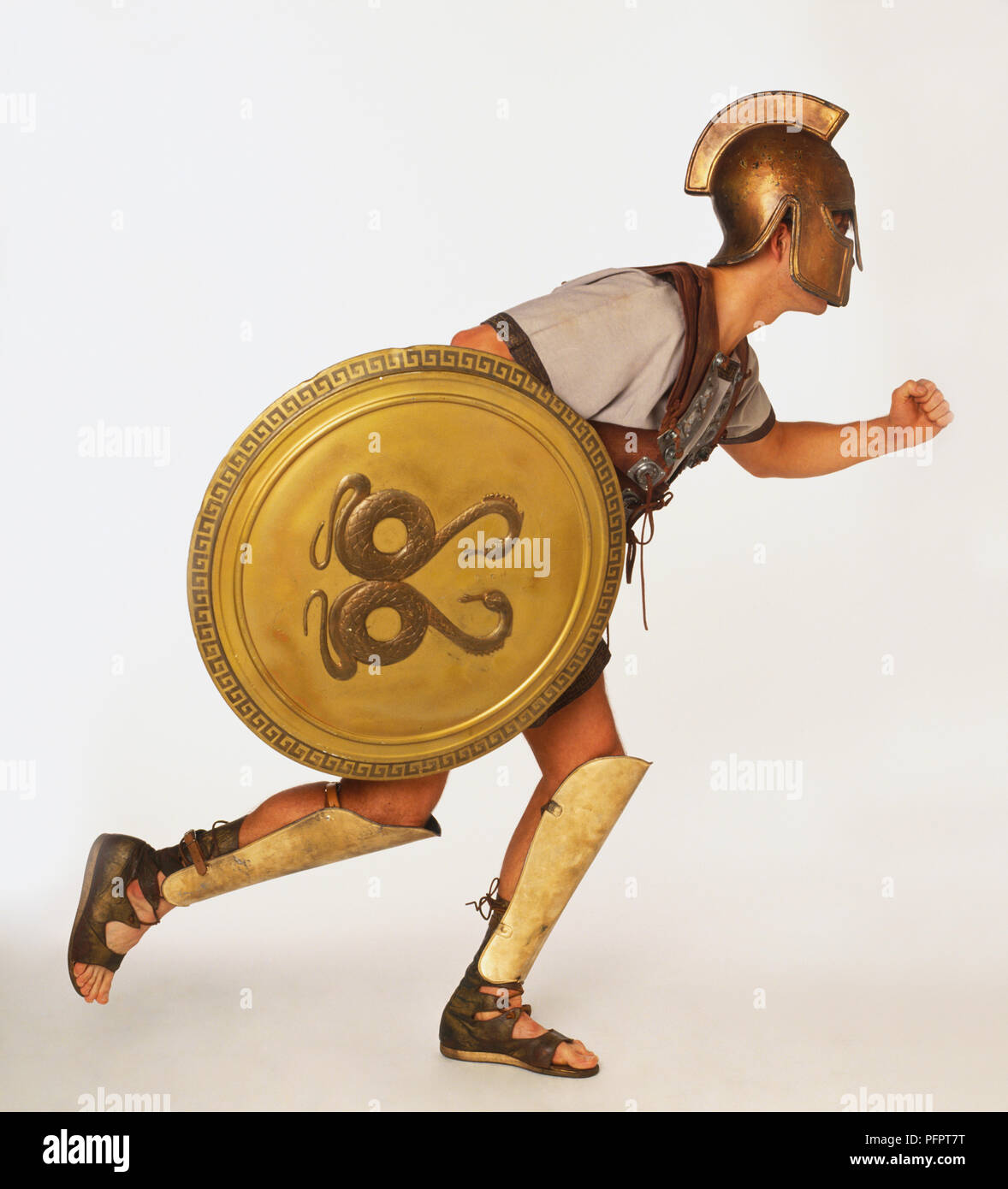 man holding shield dressed as greek warrior in running position