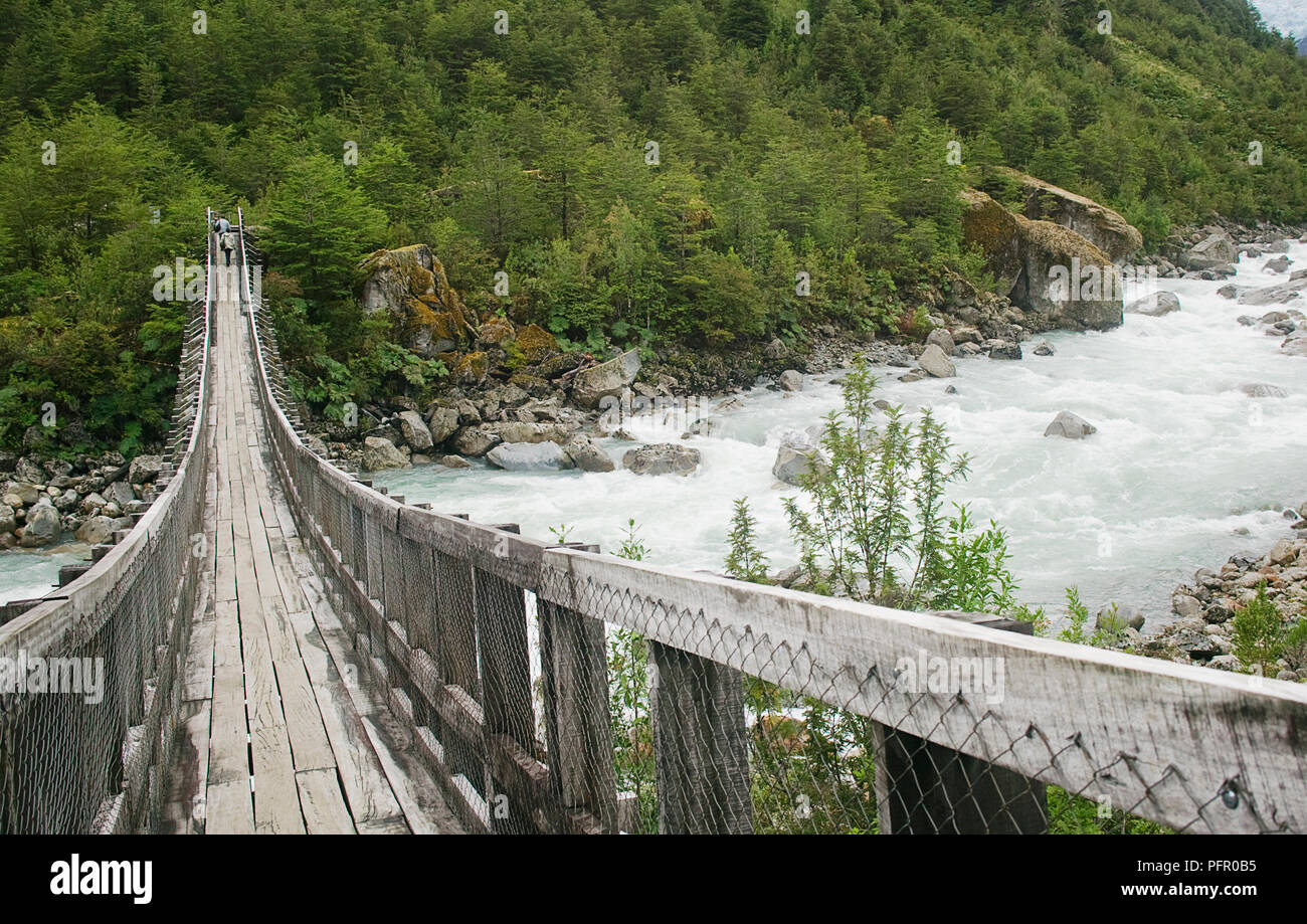 Chile, Patagonia, Queulat National Park, Ventisquero Colgante waterfall, wooden swing bridge - Stock Image