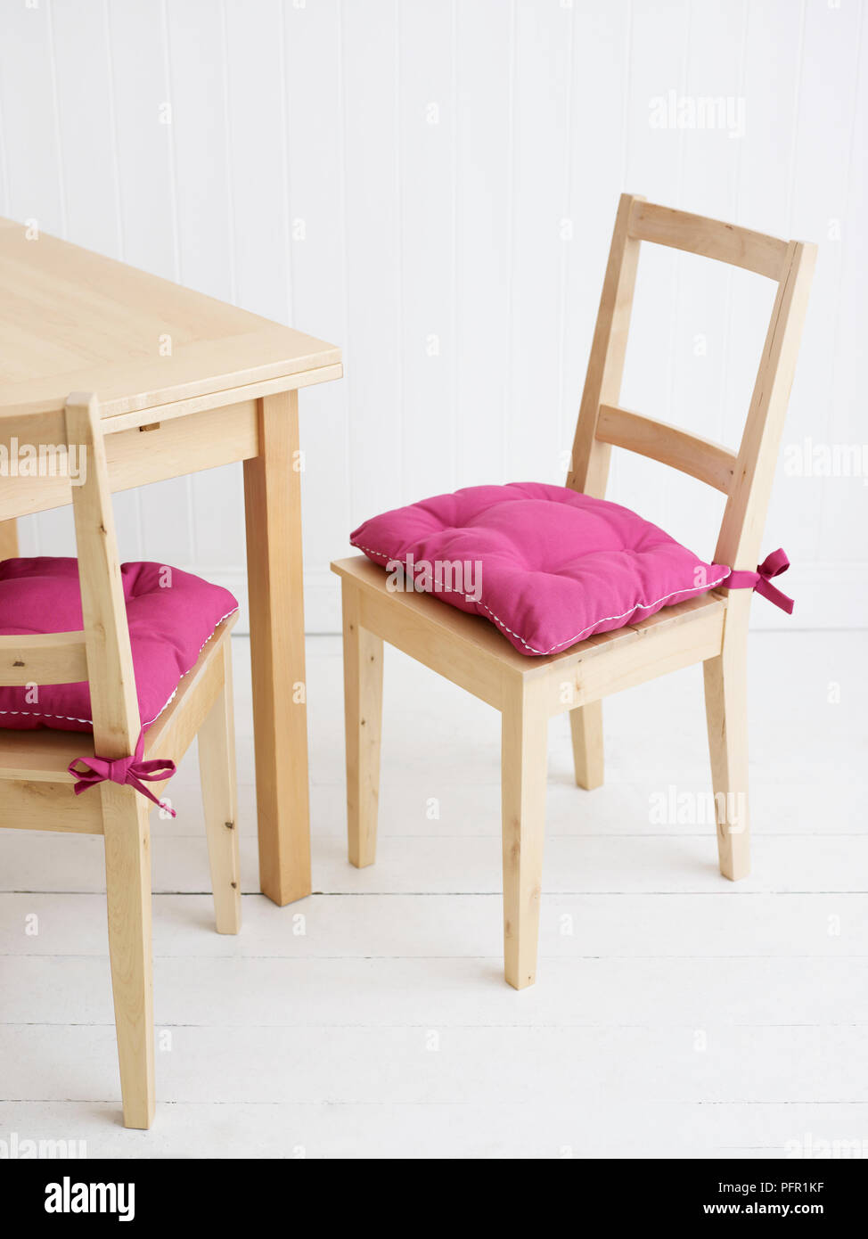 3a61ca1f258f Pink cushions on wooden chairs next to wooden kitchen table on  white-painted wooden floor