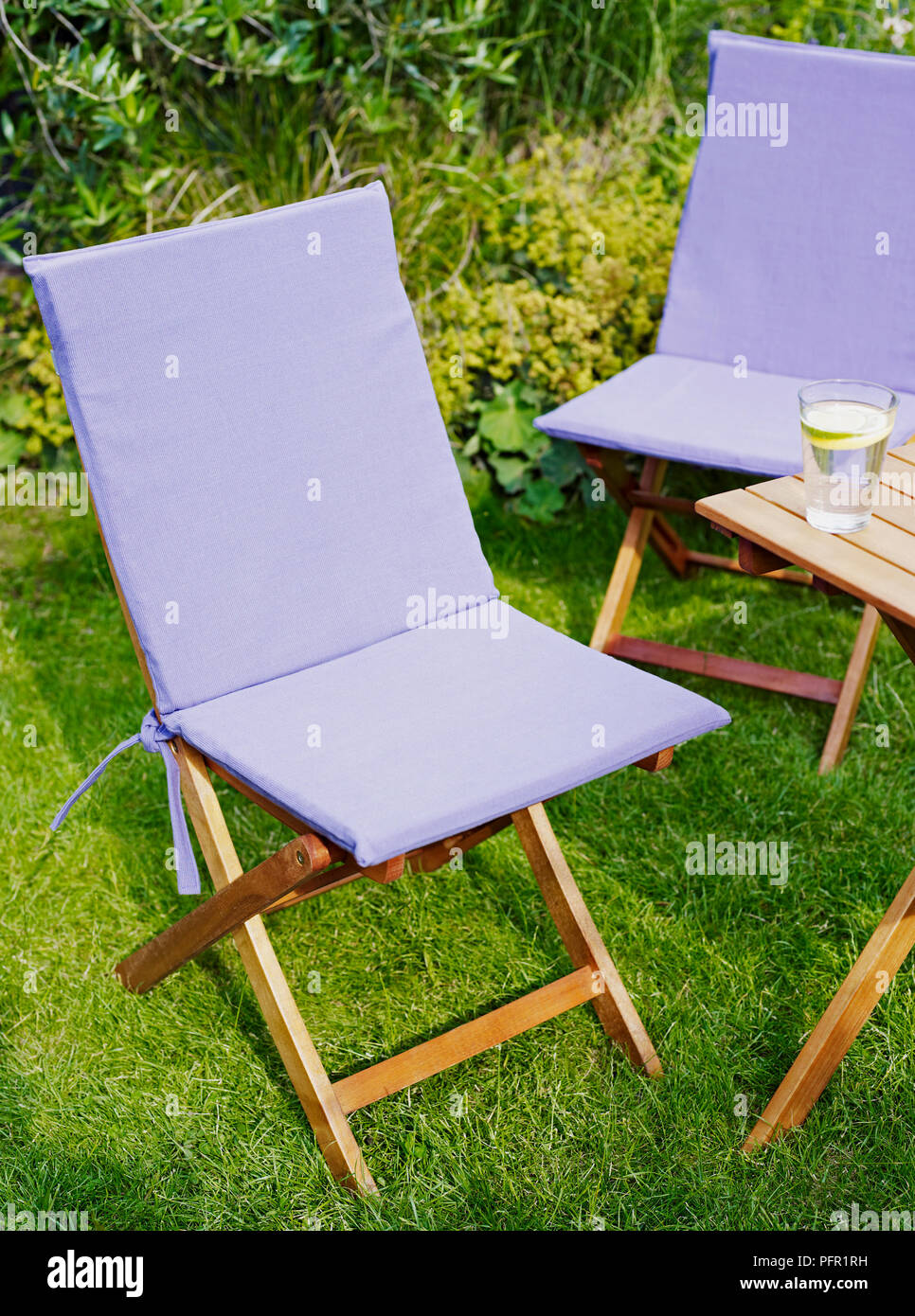 Pale purple canvas seat covers on wooden garden chairs next to