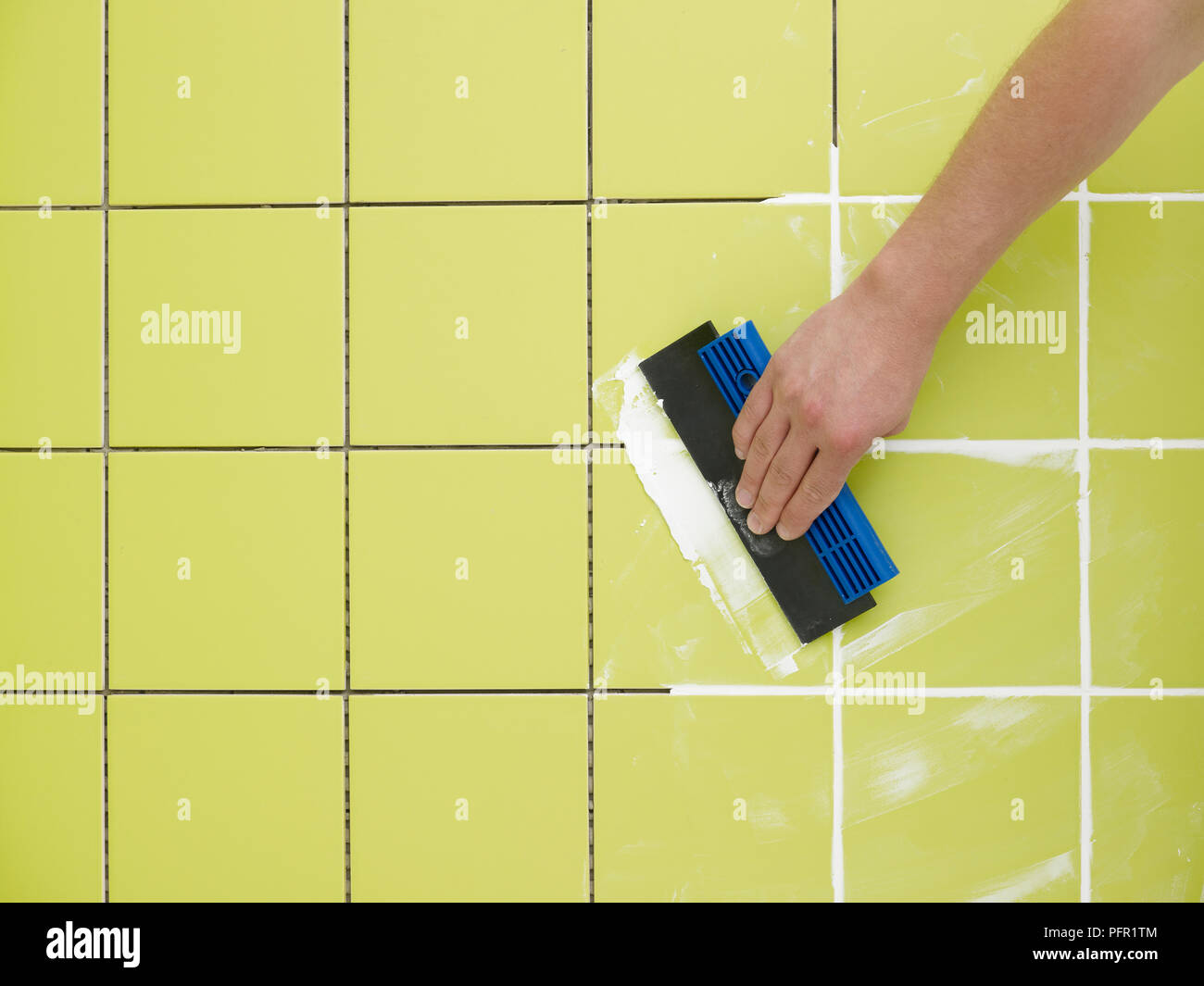 Man Grouting Ceramic Green Bathroom Tiles With Tile Grouter Stock