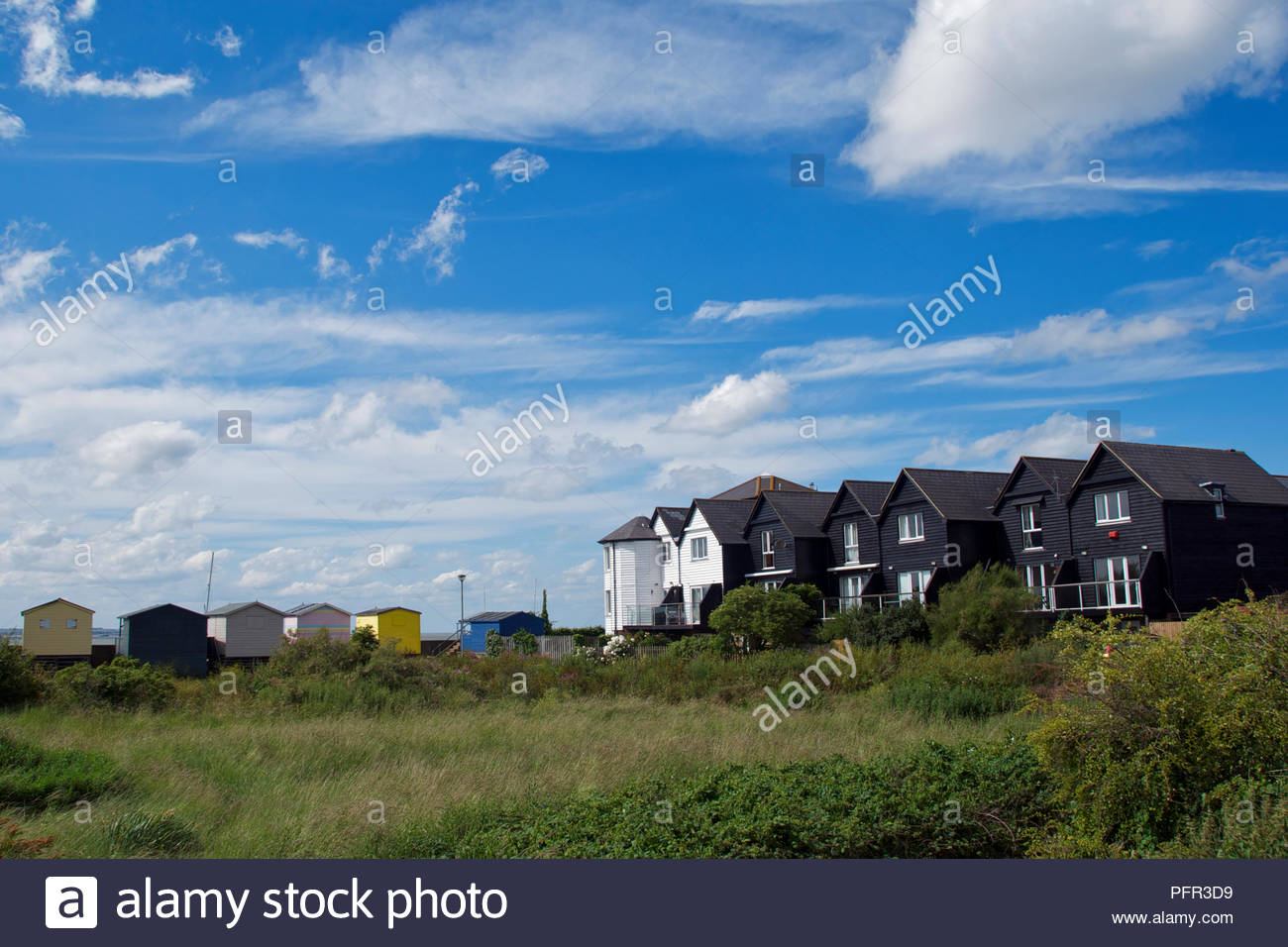 Houses on Collingwood Road and beach huts along Island Wall in Whitstable, Kent, England Stock Photo