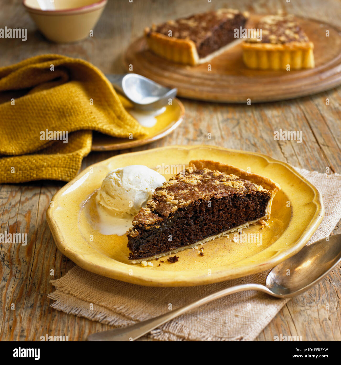 Shoo fly pie with ice cream on a plate, spoon nearby - Stock Image