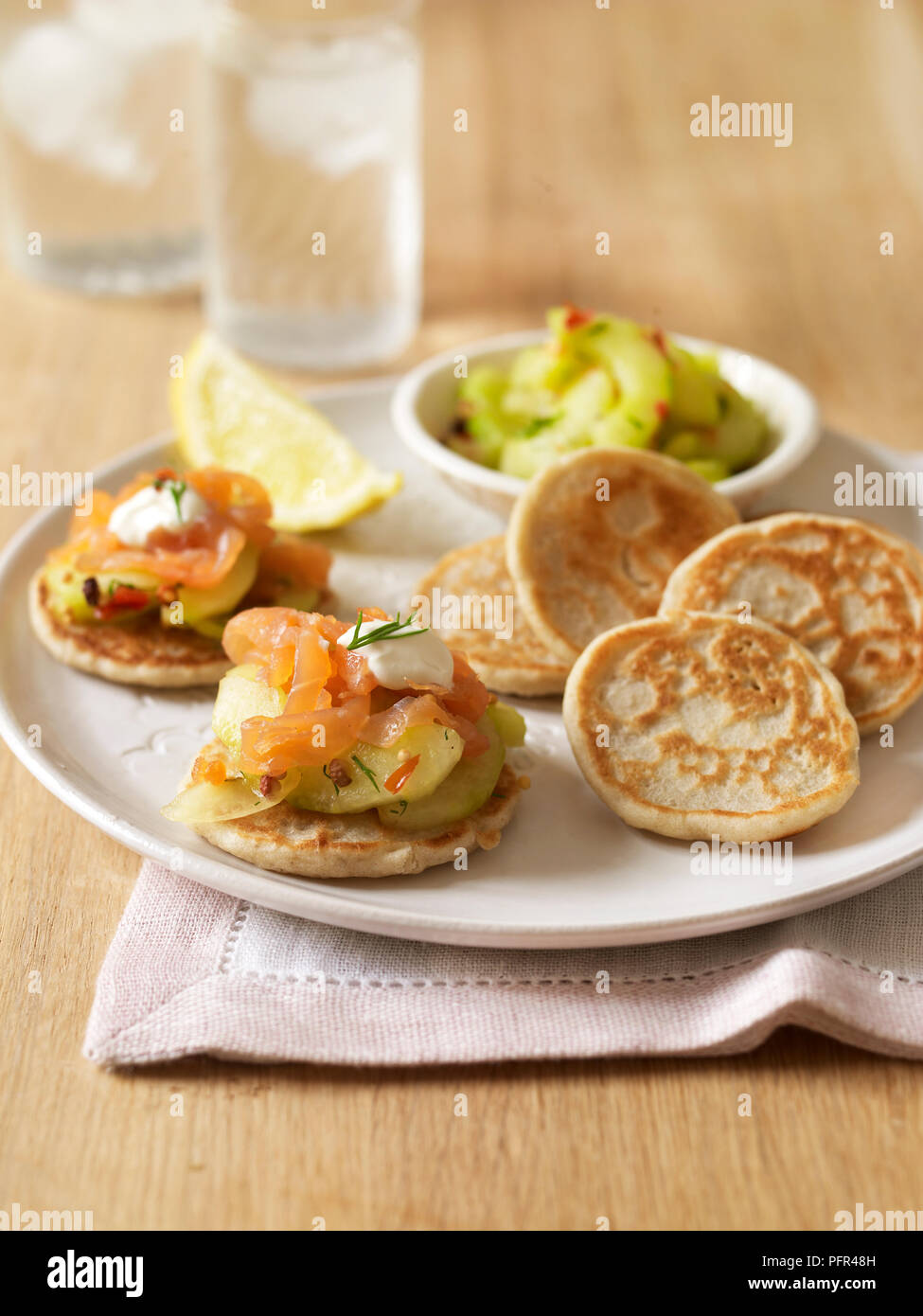 Gluten-free blinis (Russian pancakes) with smoked trout, cucumber and sour cream - Stock Image