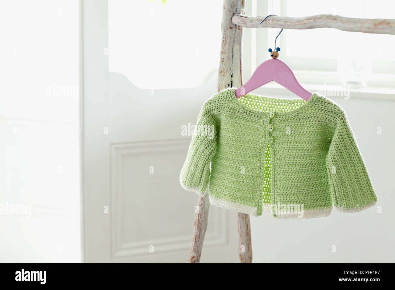 Crocheted Green Babys Cardigan With White Hem On Clothes Hanger