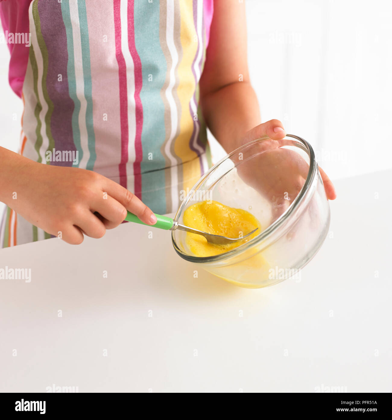 Girl beating eggs in a bowl - Stock Image