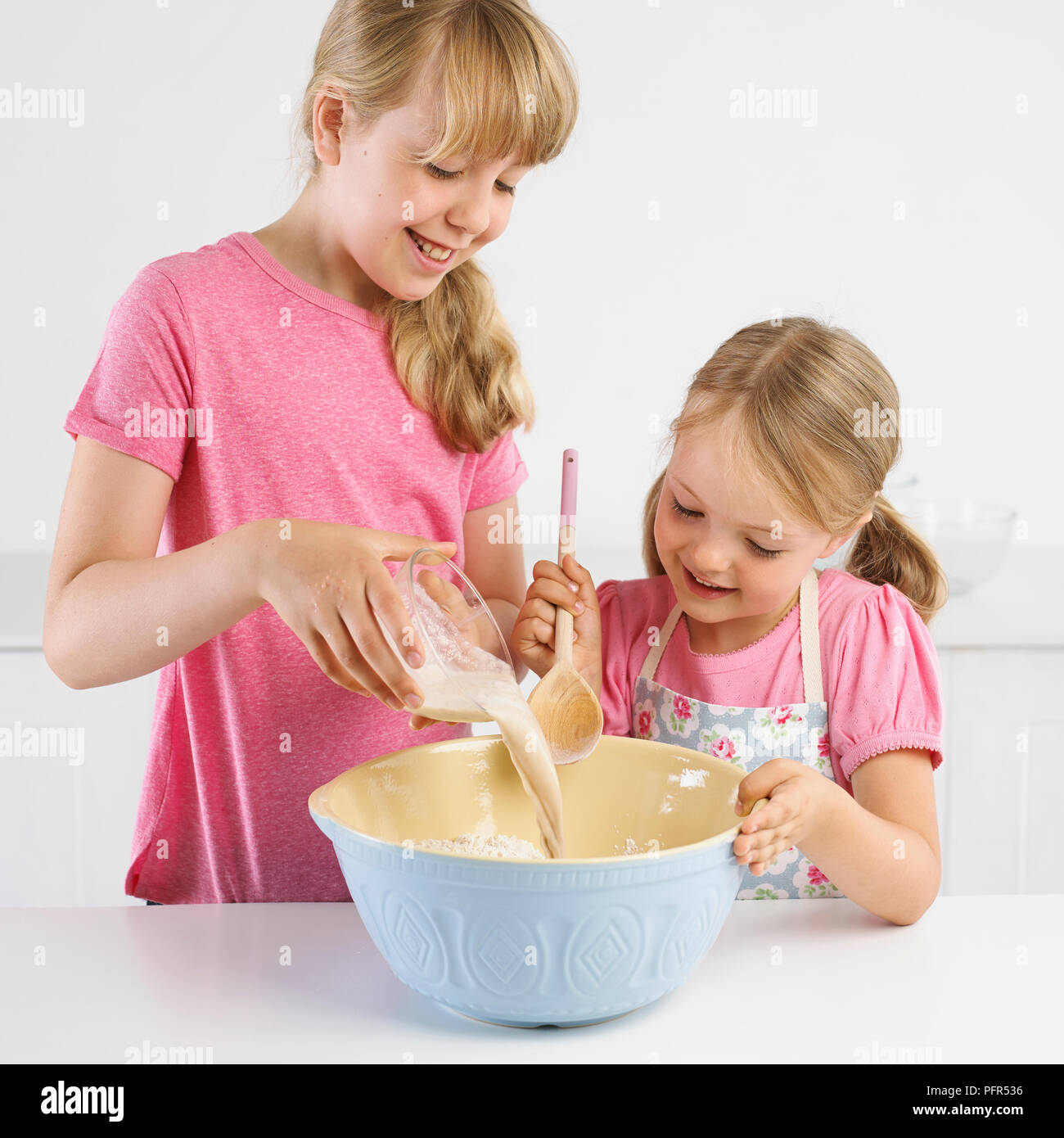 Girls pouring yeast and water mixture into bowl of flour, 5 years and 9 years - Stock Image