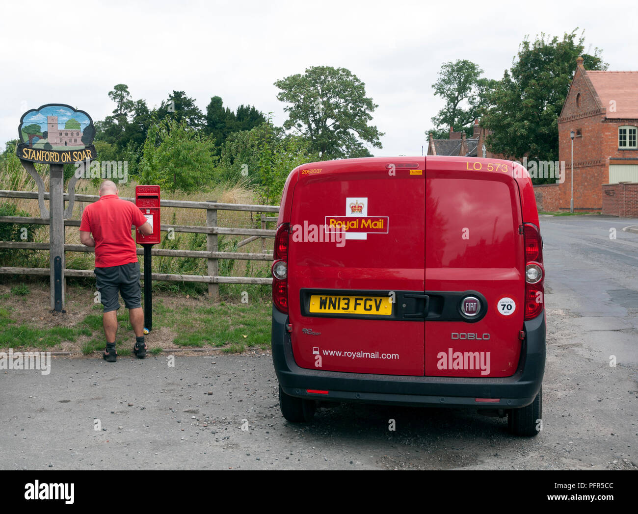 A postman emptying a postbox, Stanford-on-Soar, Nottinghamshire, England, UK - Stock Image
