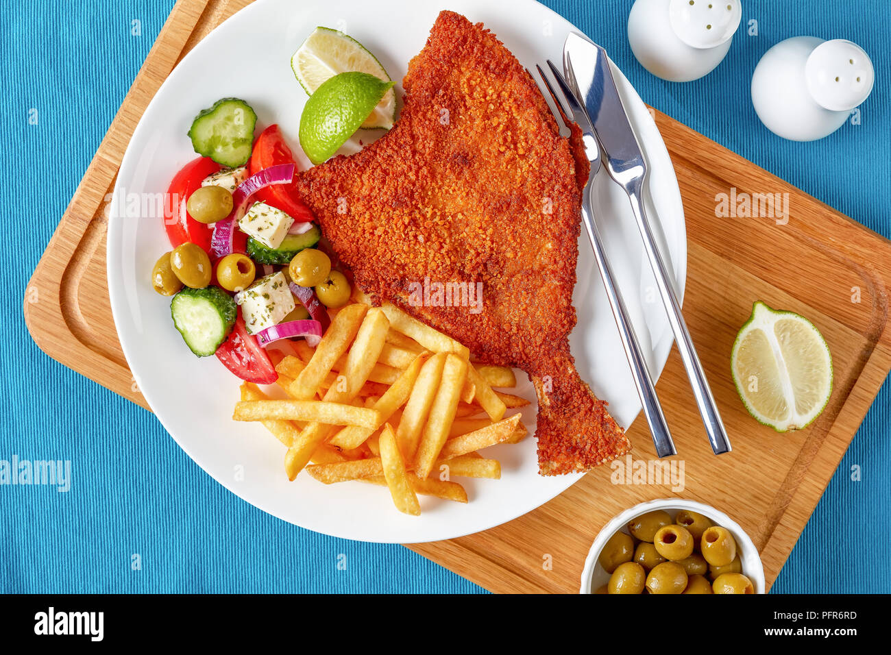 crispy fried flounder in breadcrumbs served with fresh vegetables, feta, olives greek salad and french fries on a white plate with silver fork and kni - Stock Image