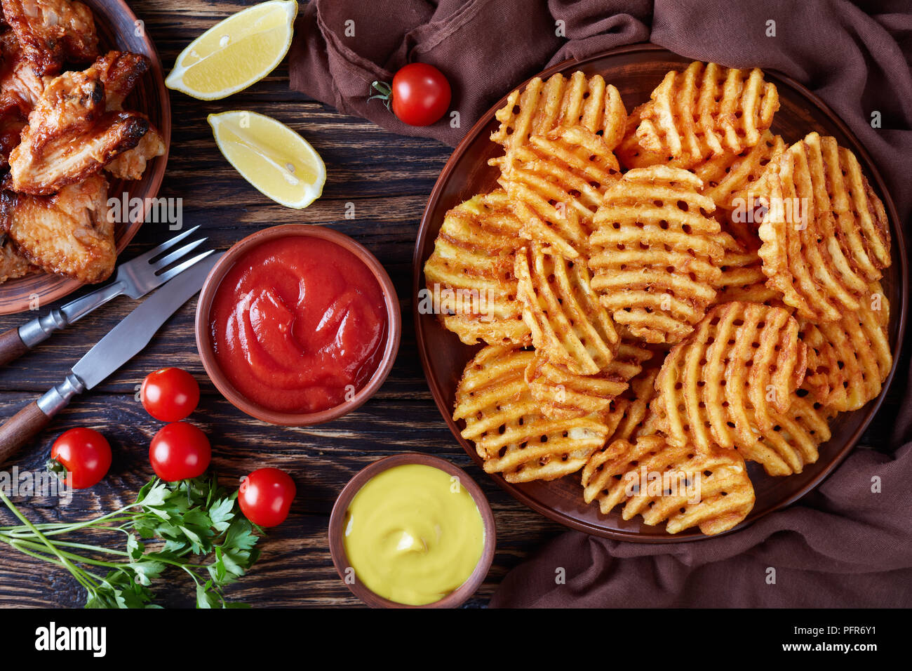 fried chicken wings and Crispy Potato Criss Cross Fries on a clay plates on a wooden table with mustard and tomato sauce dipping, view from above, fla - Stock Image