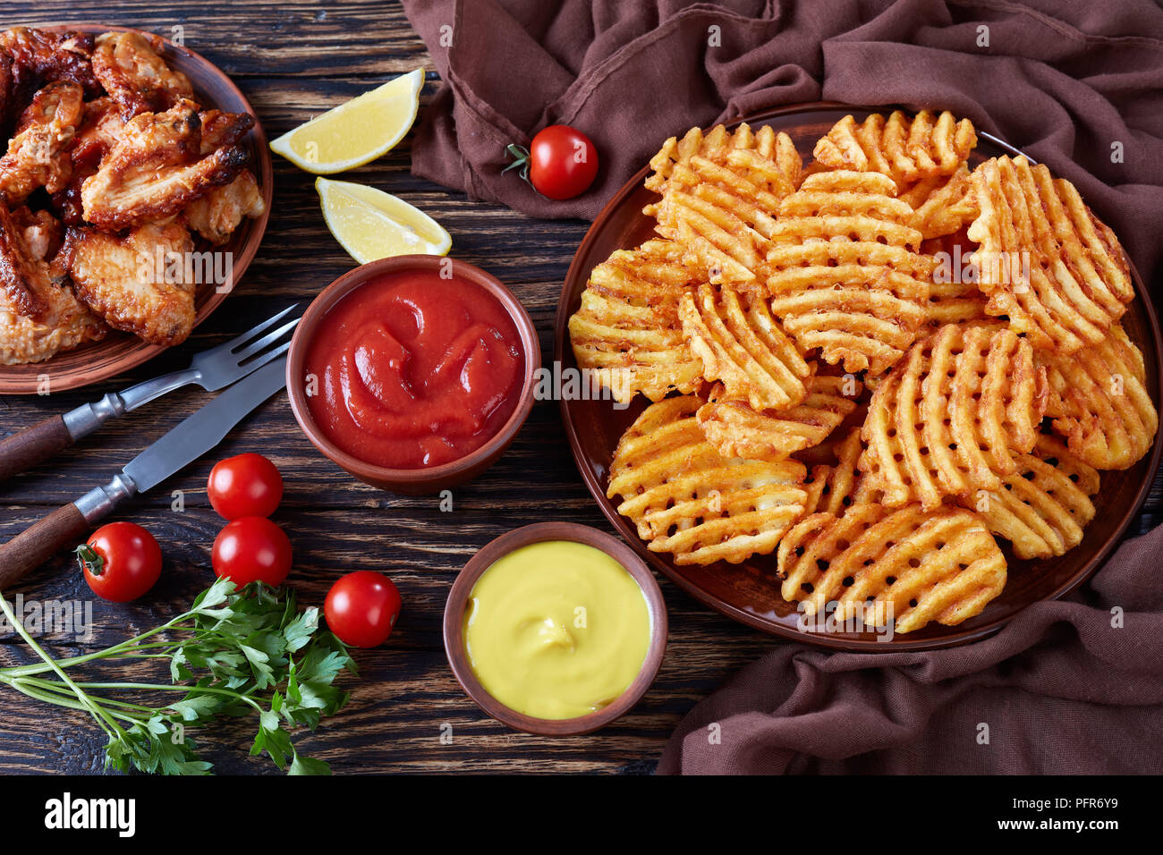 Crispy Potato Criss Cross Fries on a clay plates on a wooden table with mustard and tomato sauce dipping and sticky chicken wings at the background, v - Stock Image