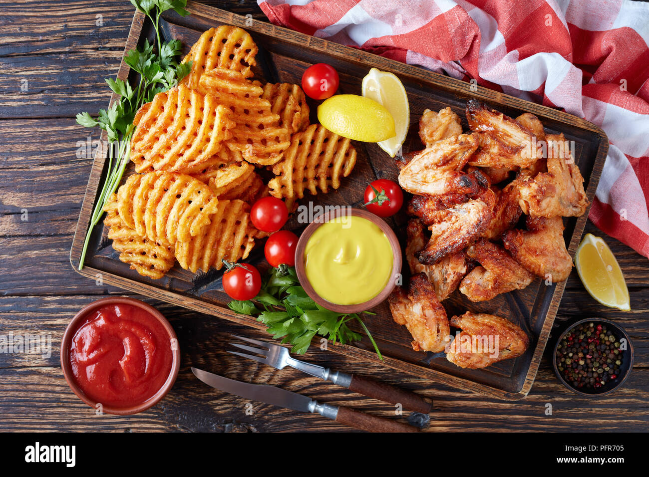 fried chicken wings, Crispy Potato Criss Cross Fries on a clay plates on a wooden table with mustard and tomato sauce dipping, view from above, close- - Stock Image
