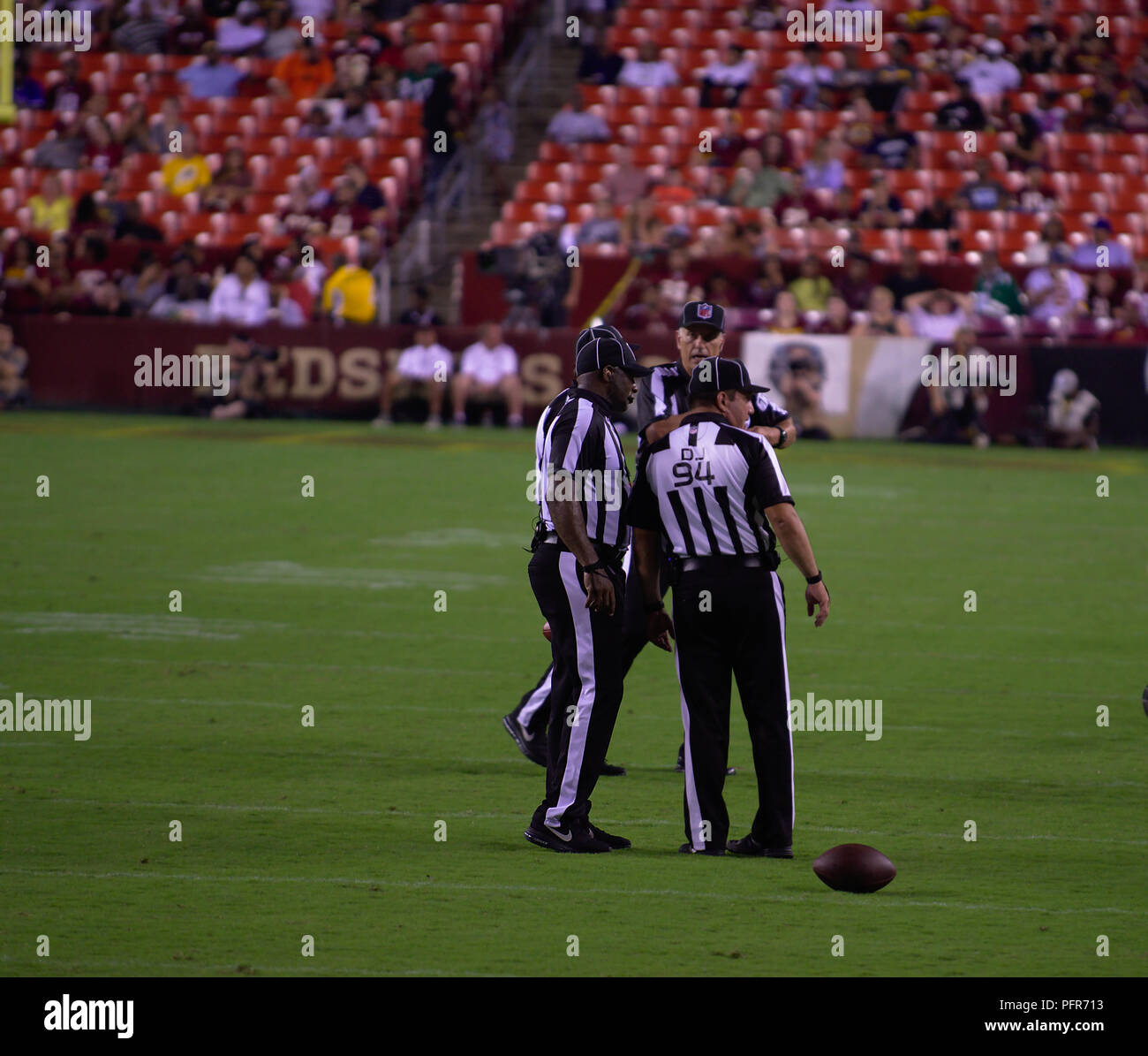Referees huddling on a call during Redskins preseason game - Stock Image