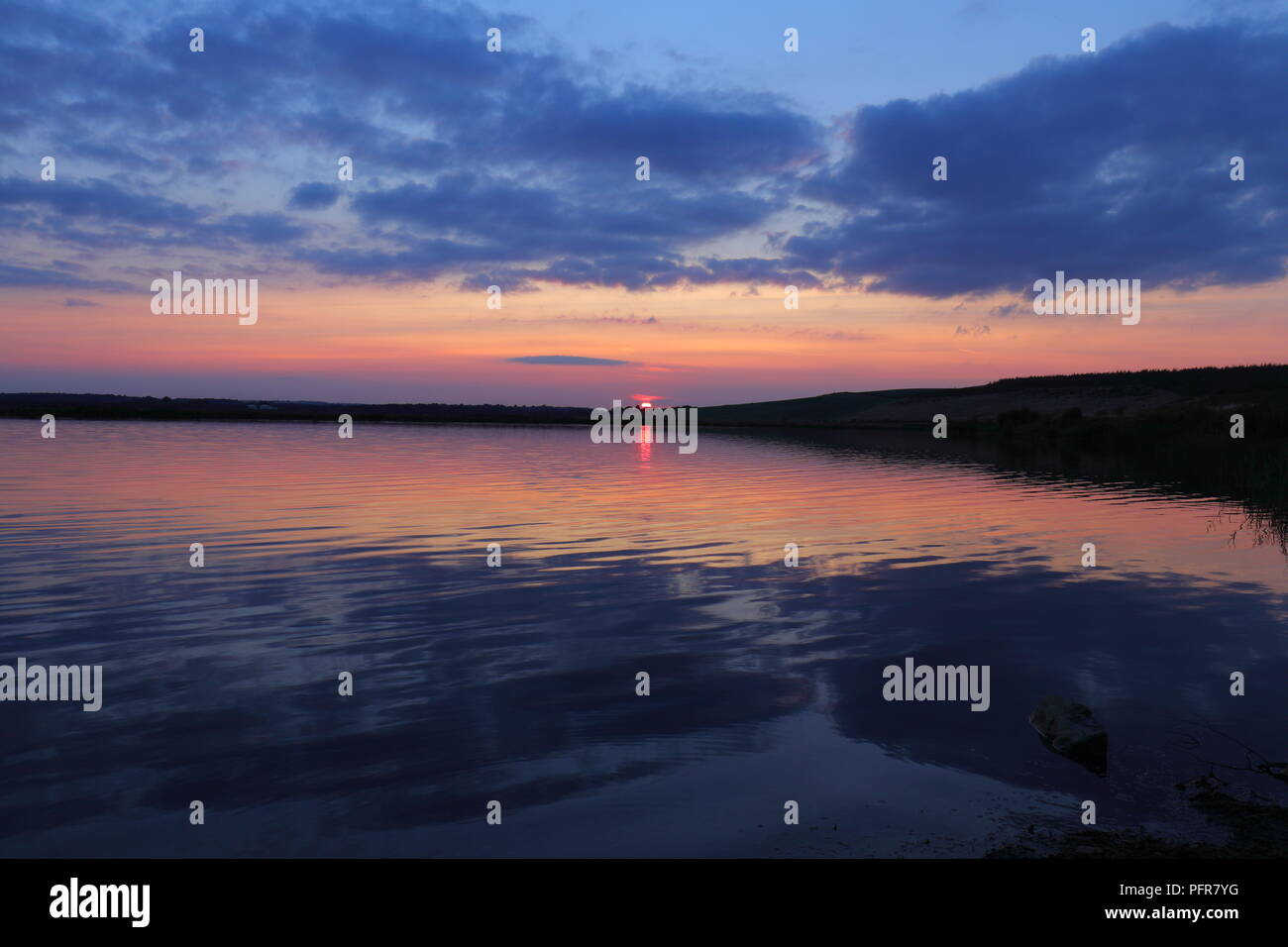 Calm water reflections of the sun setting over RSPB St Aidan's Nature Park between Leeds & Castleford - Stock Image