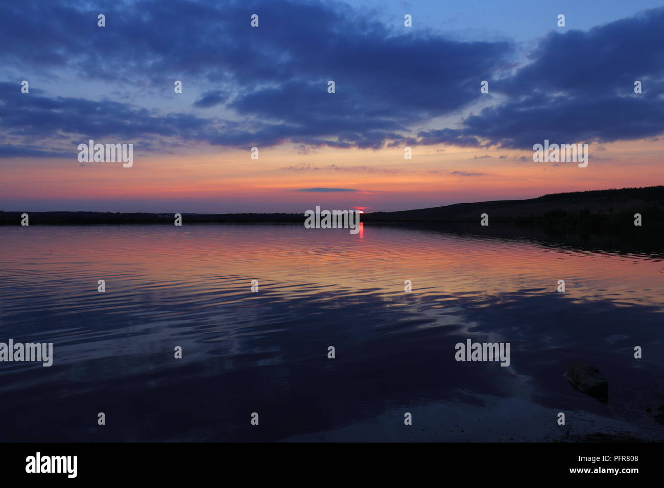 Calm water reflections of the sun setting over RSPB St Aidan's Nature Park between Leeds & Castleford Stock Photo