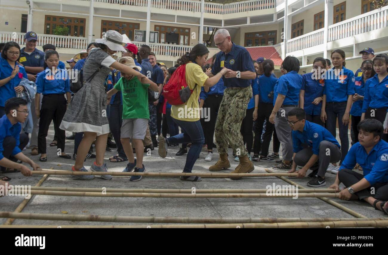 TRANG, Vietnam (May 22, 2018) Lt. Cmdr. Alan Flemming, assigned to Military Sealift Command hospital ship USNS Mercy (T-AH 19) for Pacific Partnership 2018 (PP18), plays a game with students, during a community relations culture and language exchange. PP18's mission is to work collectively with host and partner nations to enhance regional interoperability and disaster response capabilities, increase stability and security in the region, and foster new and enduring friendships across the Indo-Pacific Region. Pacific Partnership, now in its 13th iteration, is the largest annual multinational hum - Stock Image