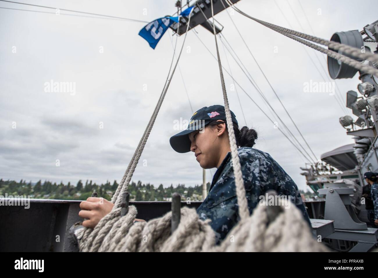 """Wash. (May 25, 2018) Airman Macey Zuniga, from Mililani Town, Hawaii, raises the """"12th Man"""" flag aboard the aircraft carrier USS John C. Stennis (CVN 74). The Seattle Seahawks football team and Sea Gals cheerleaders held a military appreciation event aboard John C. Stennis to meet and visit with Sailors. John C. Stennis is pier-side after returning to homeport after the completion of a seven-week underway where the ship's crew completed TSTA/FEP early and Carrier Strike Group 3 Group Sail in preparation for its next scheduled deployment. Stock Photo"""