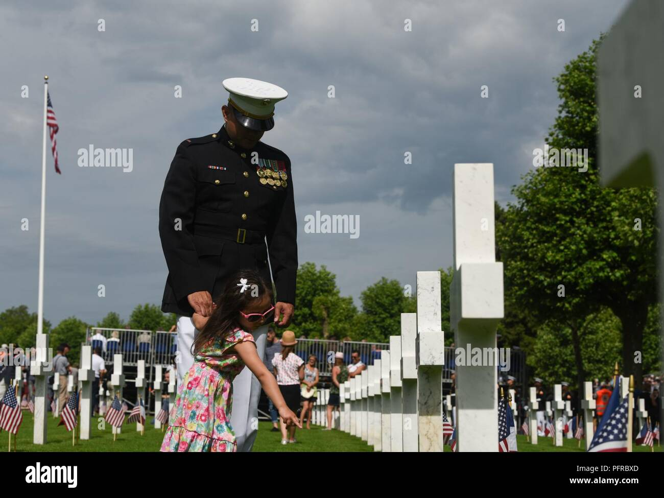 CWO4 Rene Garcia, personnel officer with Marine Forces Europe and Africa, visits headstones with his daughter during the Battle of Belleau Wood Centennial Ceremony at Aisne-Marne American Cemetery, France, May 27, 2018. The headstones belong to U.S. Marines and soldiers who fought and died in the Belleau Wood area of France during World War I. Stock Photo