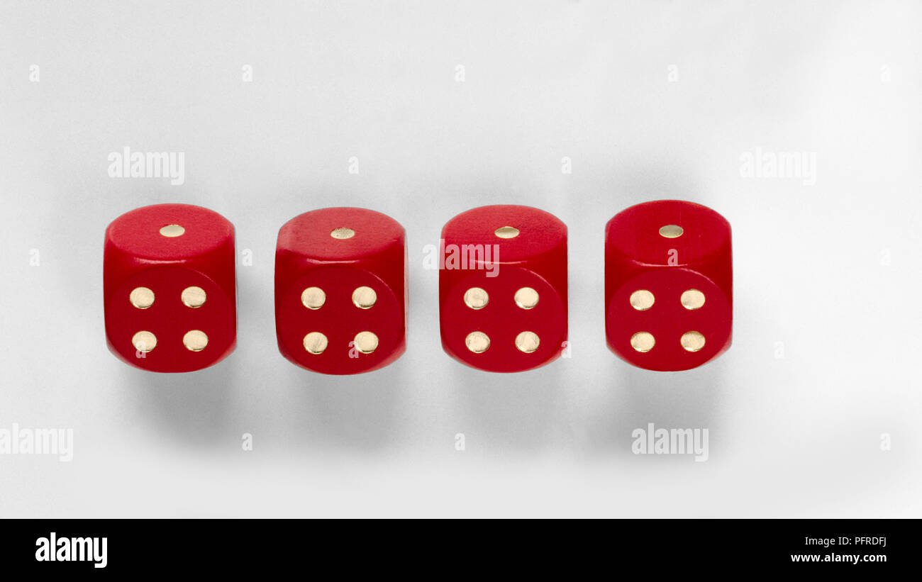 Four red dice showing the same number of dots on each face - Stock Image