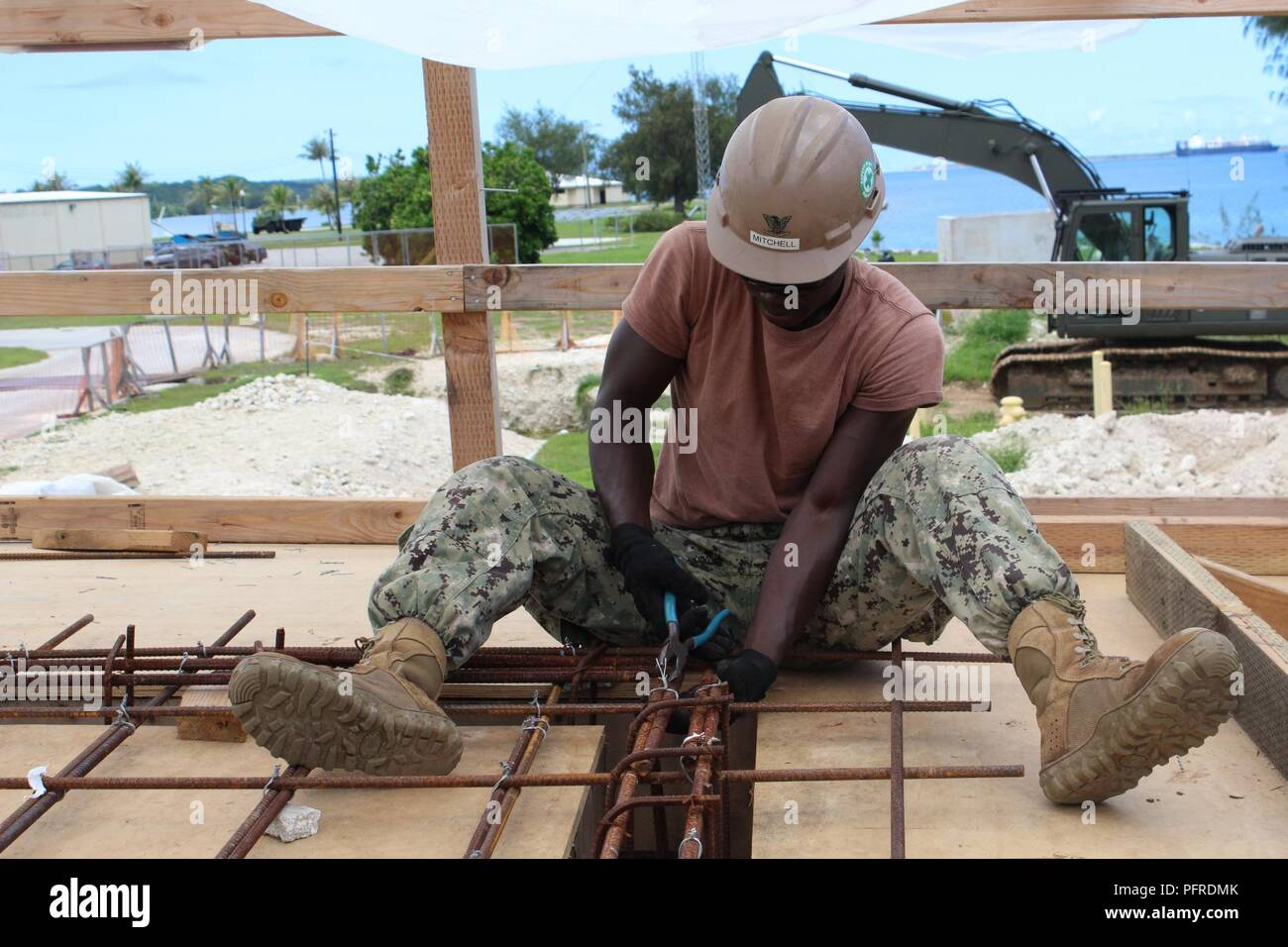 POLARIS POINT, Guam (May 21st, 2018) Construction Electrician 3rd Class Reuben Mitchell, assigned to Naval Mobile Construction Battalion (NMCB) 11, Detachment Guam, utilizes plyers to tie together reinforcing steel for a bond beam. NMCB-11 is forward deployed to execute construction, humanitarian and foreign assistance, and theater security cooperation in the 7th Fleet area of operations - Stock Image