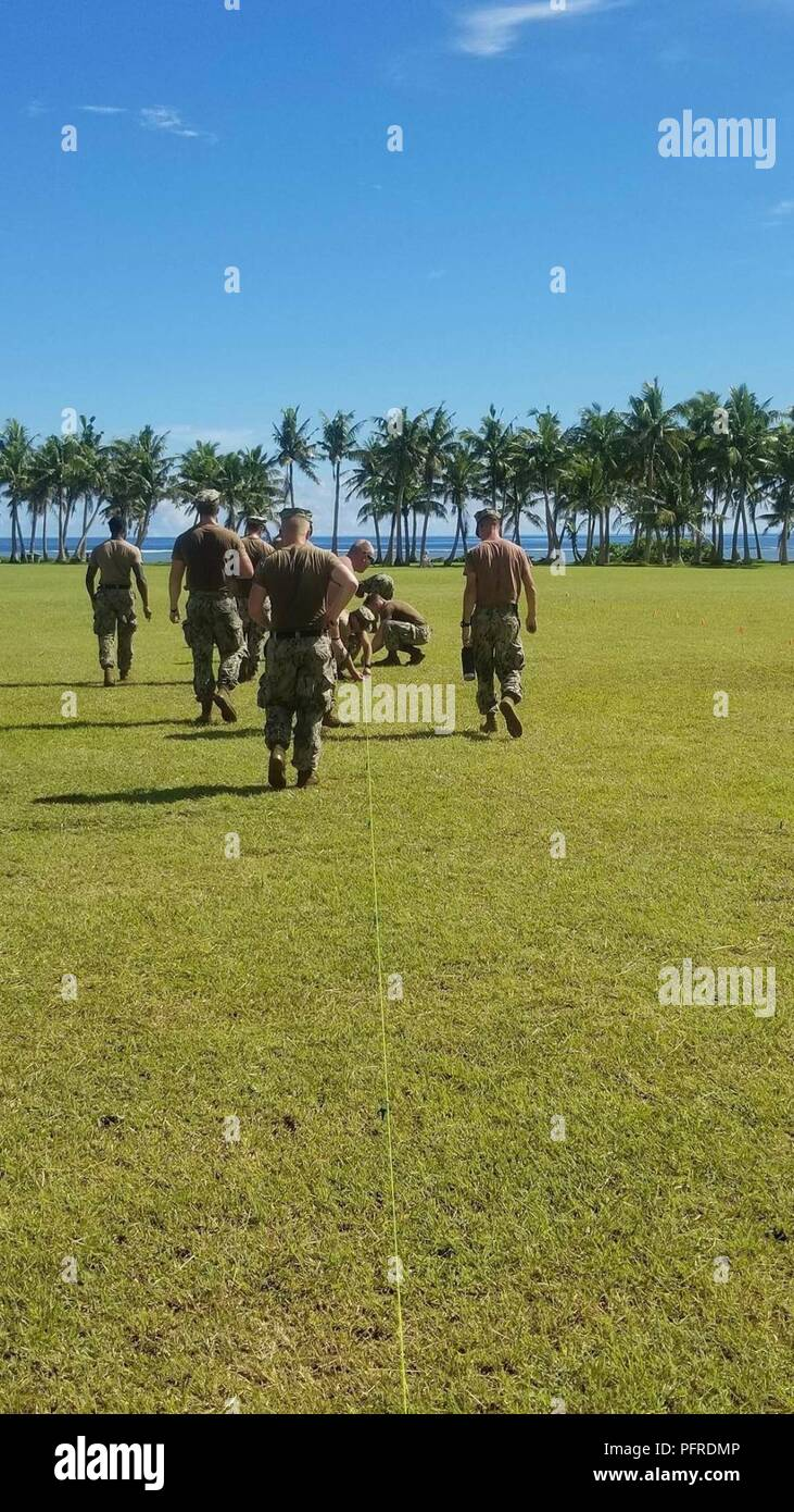 ASAN BEACH, Guam (May 21st, 2018) Seabees assigned to Naval Mobile Construction Battalion (NMCB) 11, Detachment Guam, create a grid to dig holes for memorial flags as part of the annual Memorial Day Ceremony at Asan Beach.  NMCB-11 is forward deployed to execute construction, humanitarian and foreign assistance, and theater security cooperation in the 7th Fleet area of operations. - Stock Image