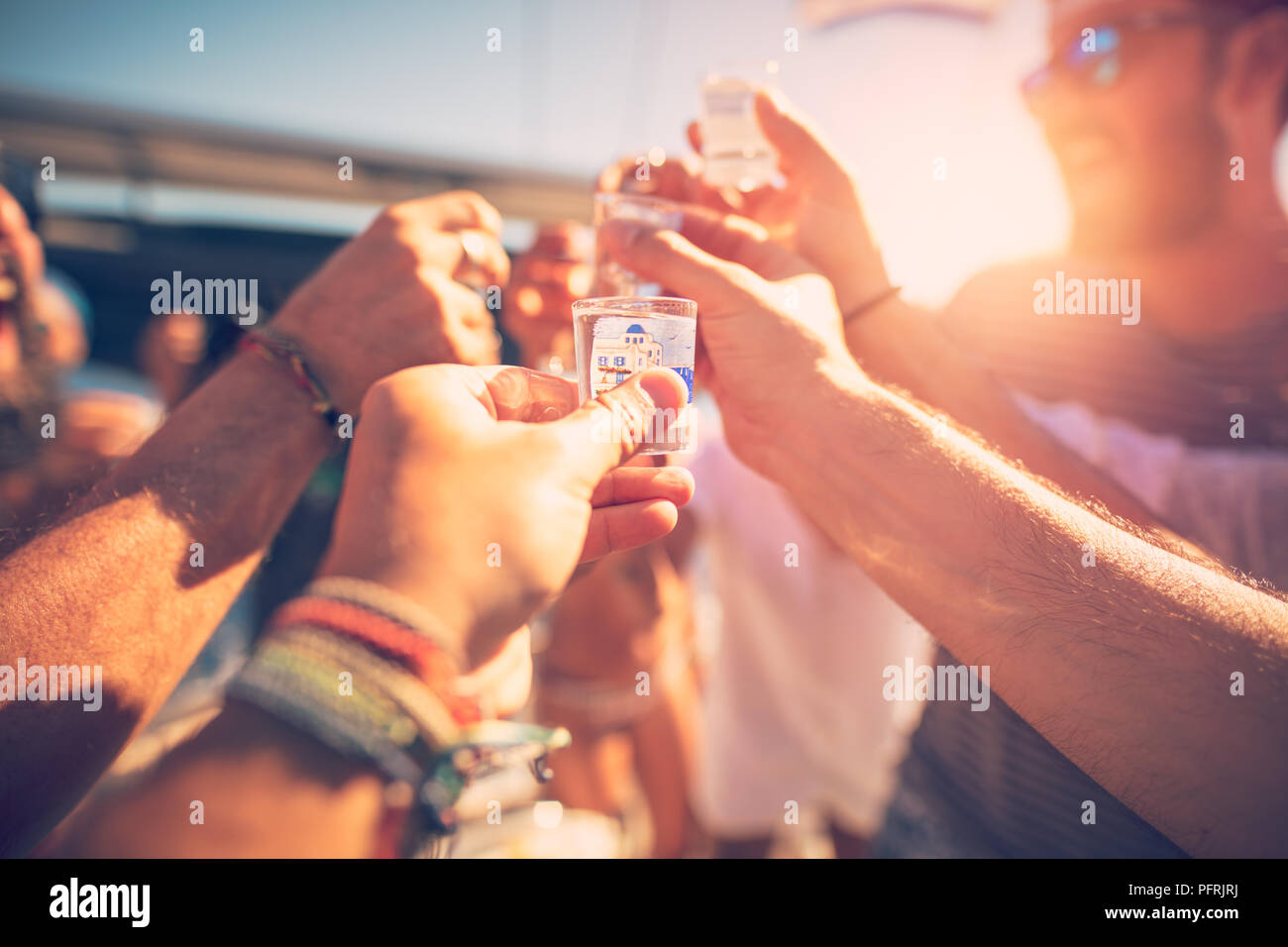 Closeup photo of a happy friends gathering together on openair party, with pleasure drinking alcohol beverage and having fun together - Stock Image
