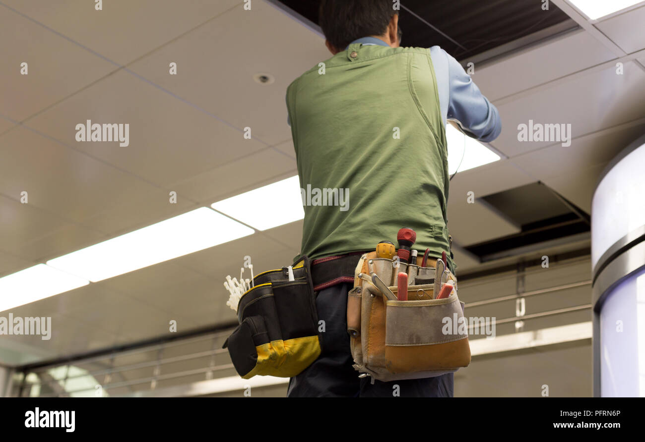 Asian Electrician Wiring A Ceiling Light In Subway Station Stock