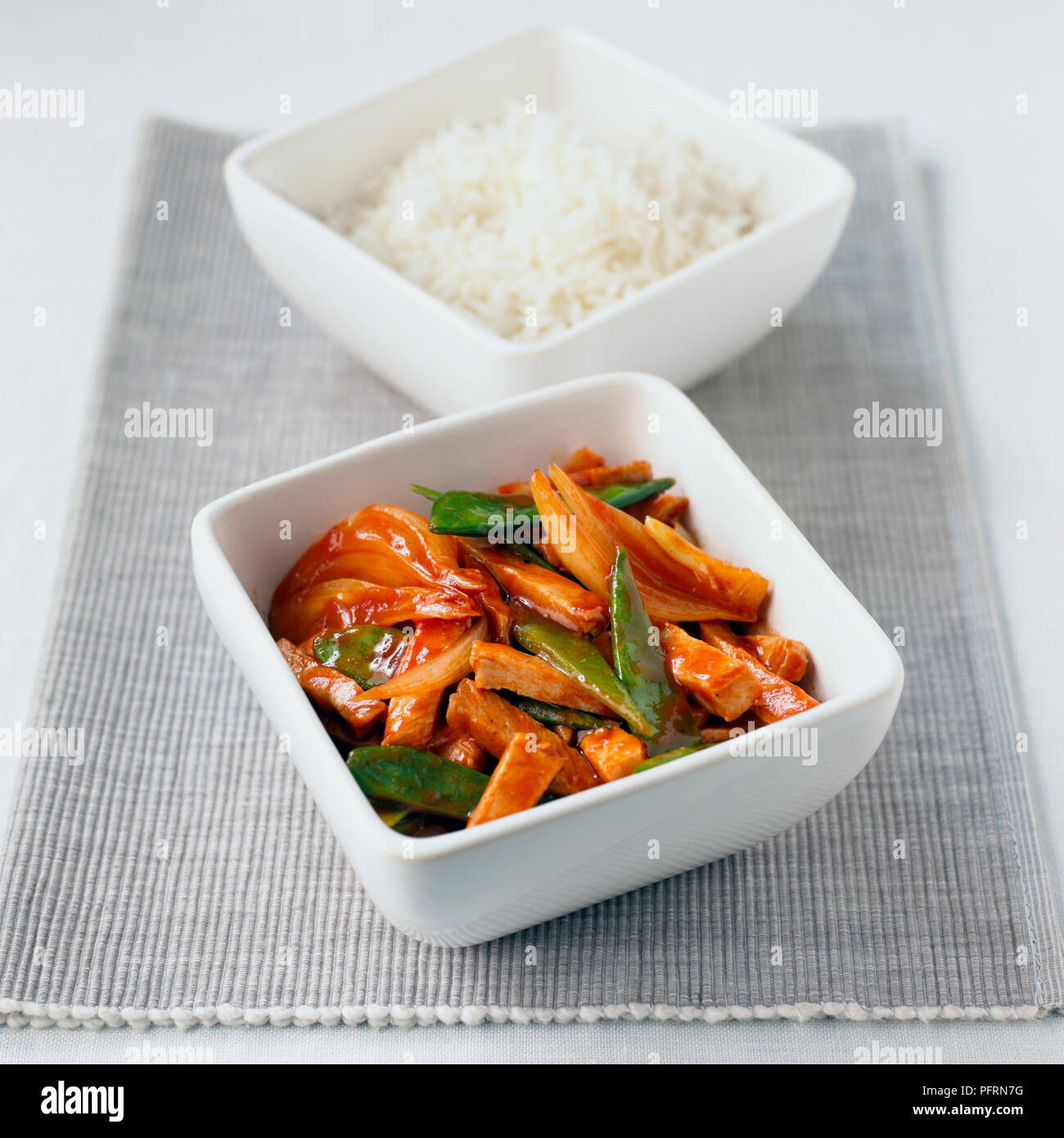Stir fried sweet and sour pork with mangetout and onion in