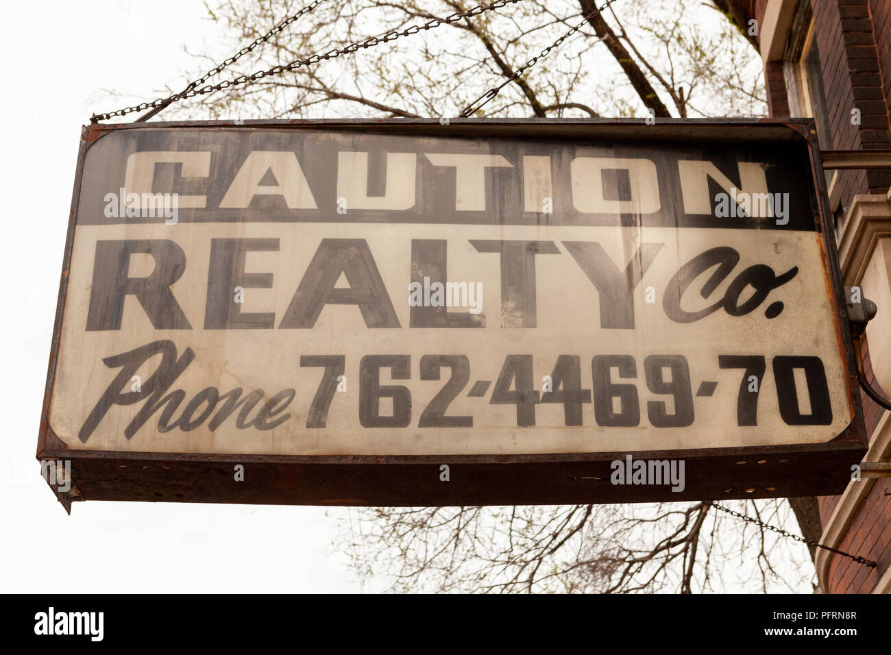 Sign attached to building on Chicago's South Side, which reads: 'Caution Realty Co. (followed by phone number).' - Stock Image