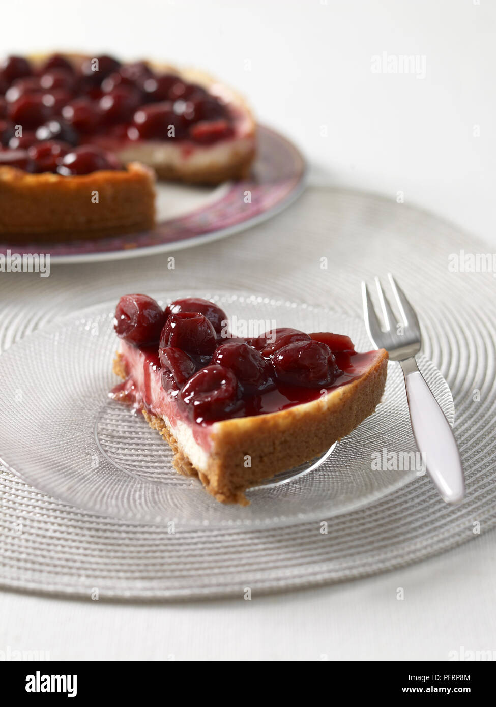 Cheery cheesecake slice on glass plate, with a dessert fork nearby - Stock Image