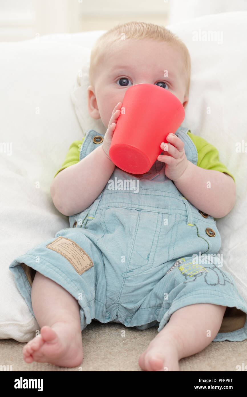 d4dd36cd1 Baby boy (17 weeks) holding red plastic cup in front of his face ...