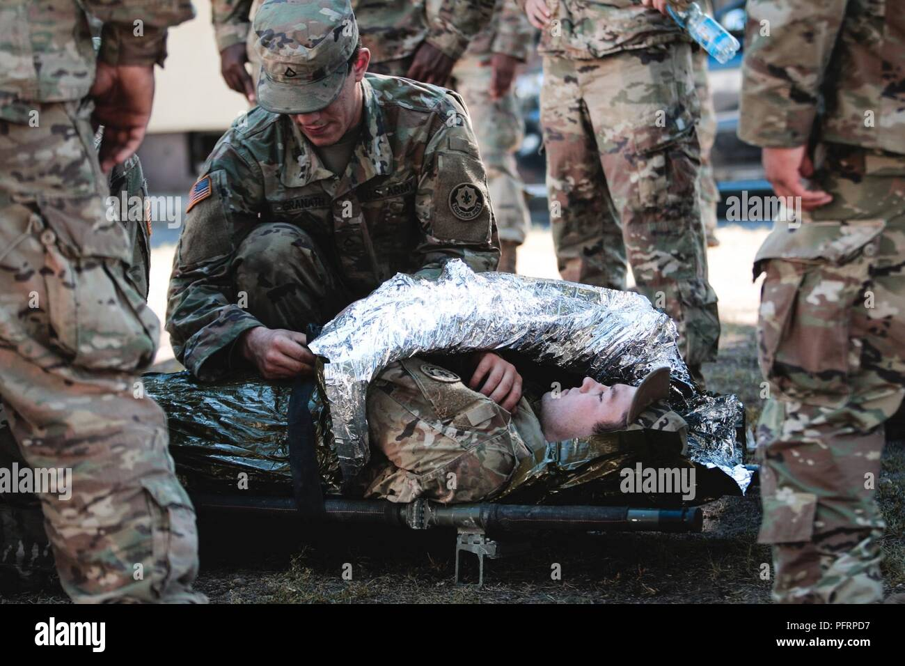 Pfc. Grant Granath (left) and Pfc. Jakob Willams (right), infantrymen assigned to1st Squadron, 2nd Cavalry Regiment, practice preparing a casualty for evacuation during combat lifesaver training withBattle Group Poland at Bemowo Piskie Training Area, Poland,May 30, 2018. Battle Group Poland is a unique, multinational coalition of U.S., U.K., Croatian and Romanian Soldiers who serve with the Polish 15th Mechanized Brigade as a deterrence force in support of NATO's Enhanced Forward Presence. Stock Photo