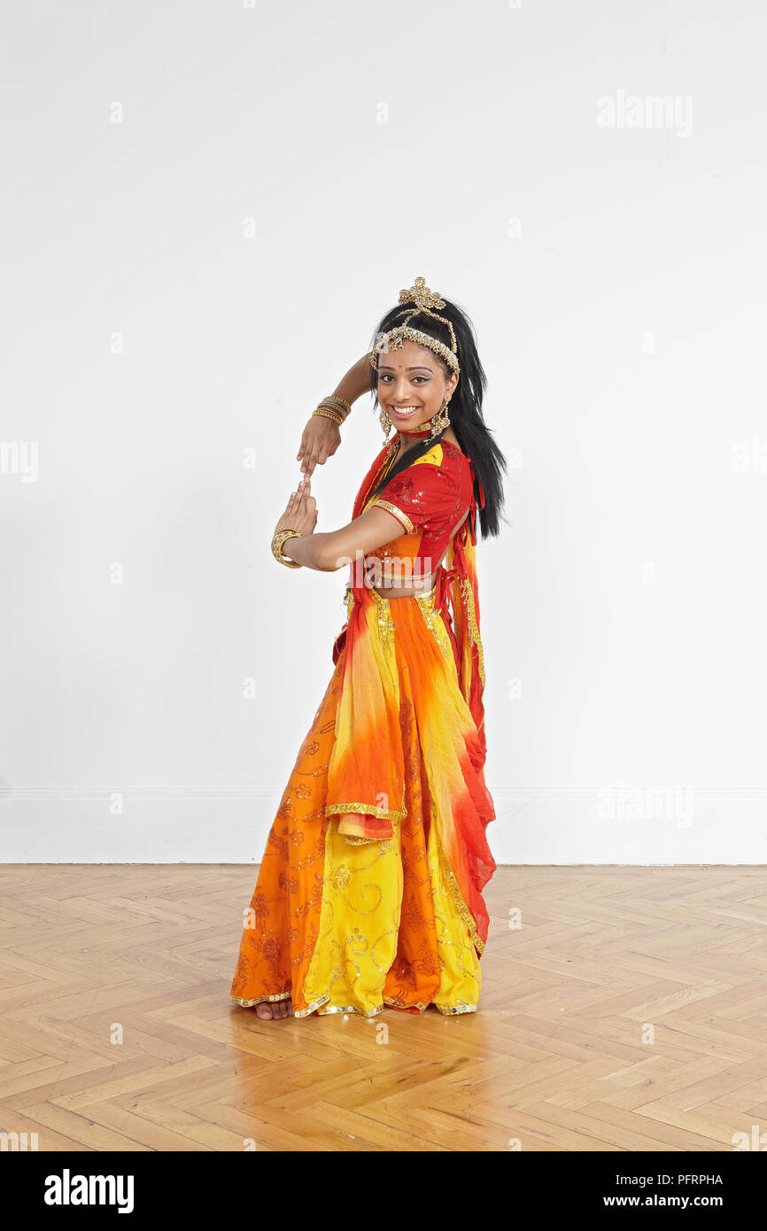 a9ca953e602f8 Teenage girl performing Bollywood dance move (hands facing each other)