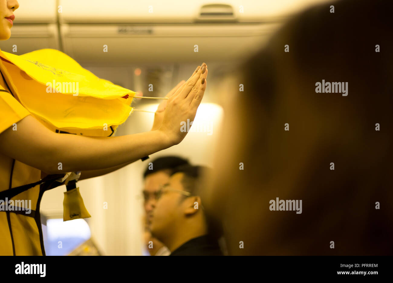 Flight attendant presenting a life vest on board  - Stock Image