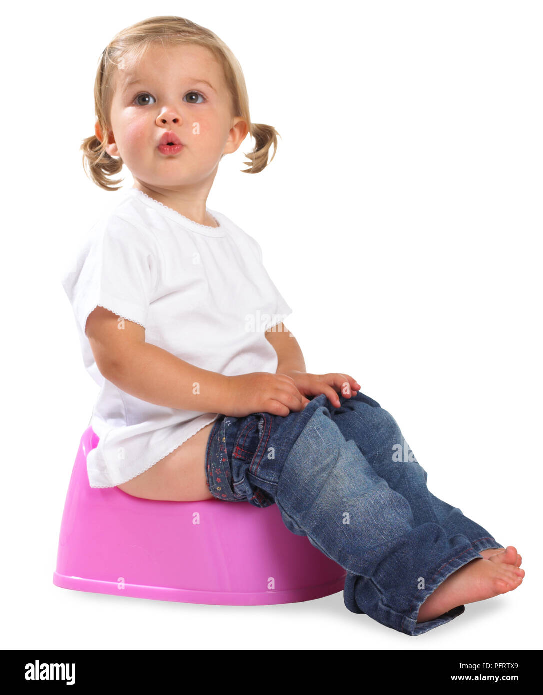 Girl sitting on pink potty, 1.5 years - Stock Image