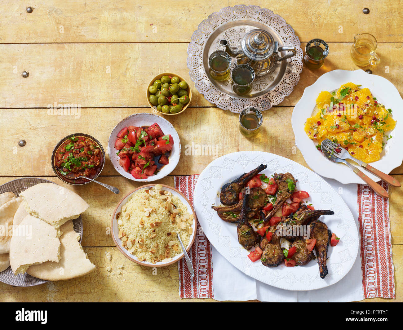 Moroccan dinner, including zahlouk (aubergine dip), kesra (bread), kesksou (couscous), lahma meshwi (lamb), olives, mint tea, salade d'oranges a la marocaine - Stock Image
