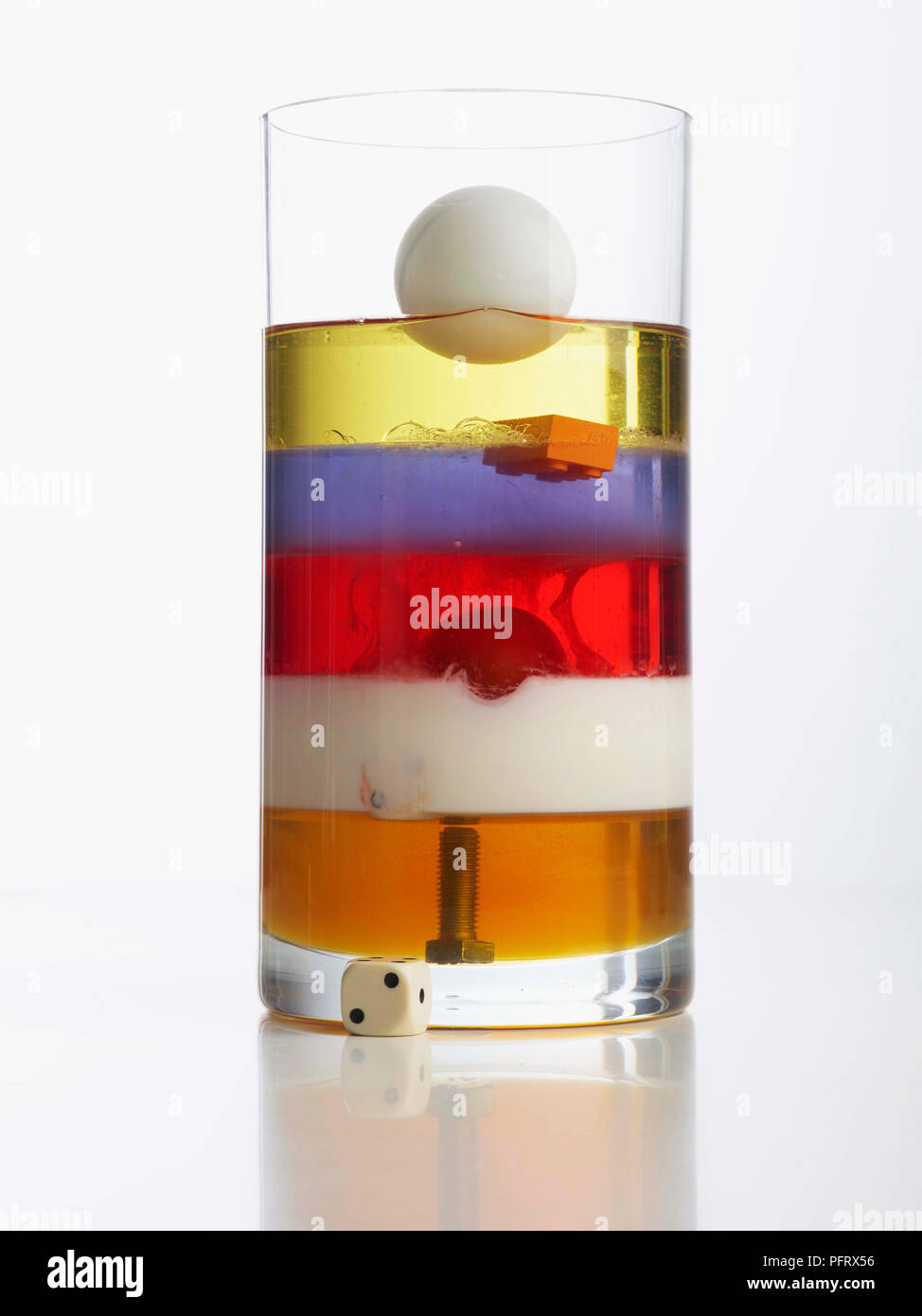 Density tower showing vase with 5 layers: honey, milk, washing-up liquid, water, vegetable oil. Bolt, cherry tomato, and table tennis ball are also in the vase. - Stock Image