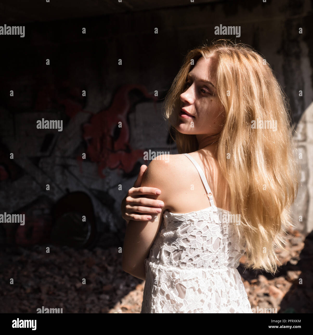 lonely blondy woman in a whit translucent blouse in abandoned building - Stock Image